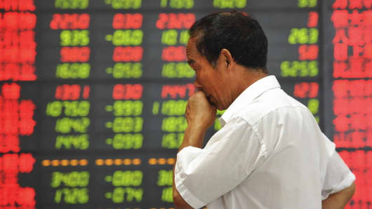 An investor in front of an electronic board showing stock information at a brokerage house in Fuyang, China, July 28, 2015.
