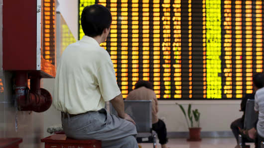An investor watches stock prices in Shanghai, China.
