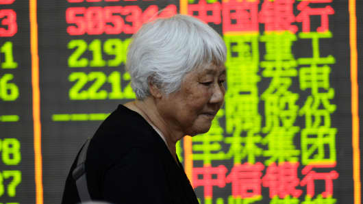 An investor observes an electric screen at a stock exchange hall on July 28, 2015 in Hangzhou, China.