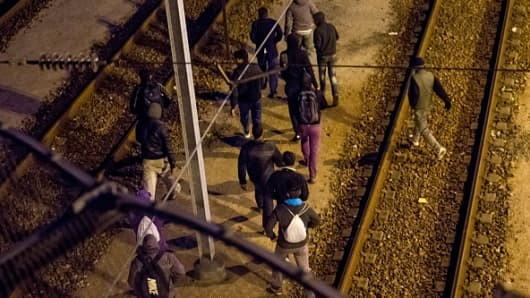 Migrants walk along railway tracks at the Eurotunnel terminal on July 28, 2015.