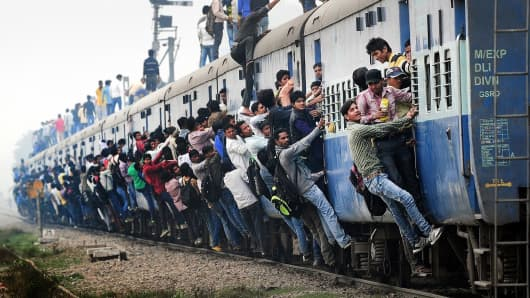 Indian passengers stand and hang onto a train as it departs from a station on the outskirts of New Delhi.