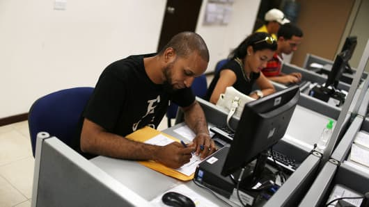 Edwin Medina (L) and Coral Tapia use the resources available to look for work at an unemployment office a day after the governor gave a televised speech regarding the government's $72 billion debt on June 30, 2015 in San Juan, Puerto Rico.