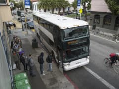 Google Inc. employees board a bus that will take them to the company's campus, in Mountain View, California, from San Francisco.