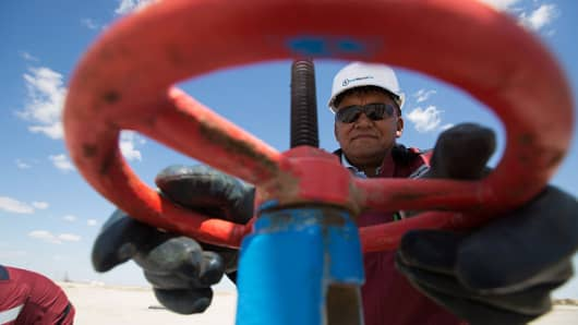 An oil worker adjusts a flow valve at an oilfield operated by Embamunaigas, a unit of KazMunaiGas Exploration Production, near Atyrau, Kazakhstan.