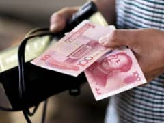 A customer holds a 100 Yuan note at a market in Beijing, August 12, 2015.