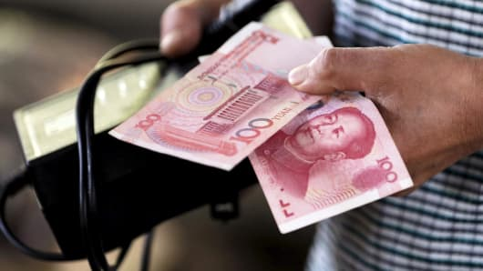 A customer holds a 100 Yuan note at a market in Beijing.