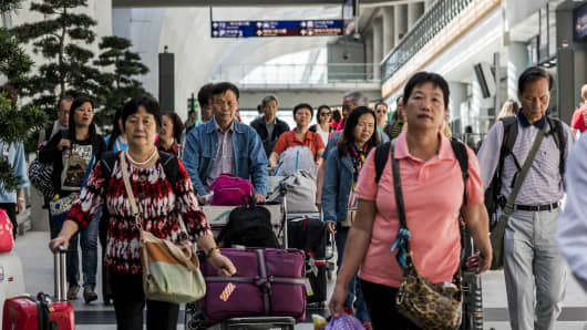 People walk through a concourse with their luggage at Hong Kong International Airport.