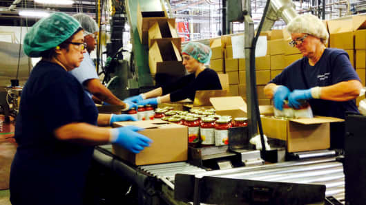 Workers box jars of pasta sauce at a plant run by Chelten House Products in Bridgeport, N.J.