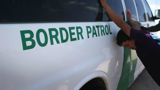 Border Patrol agents detain undocumented immigrants after they crossed the border from Mexico into the United States on August 7, 2015, in McAllen, Texas.