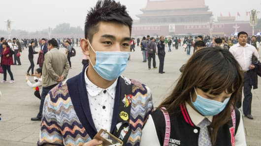 A couple wear face masks in Tiananmen Square in Beijing.