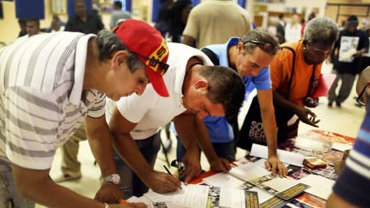 People fill out a form for available job opportunities during the Miami Worldcenter construction job fair in Miami, last month.
