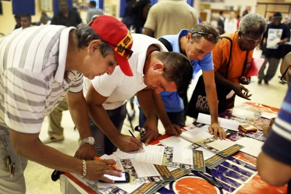 People fill out a form for job opportunities during the Miami Worldcenter construction job fair.