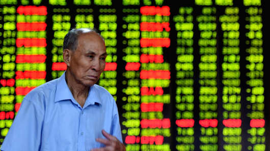 An investor looks through stock infomation at a securities firm in Haikou, capital of south China's Hainan Province.