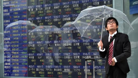 A businessman with an umbrella looks up to the rainy sky as he passes a share prices board in Tokyo, Japan.