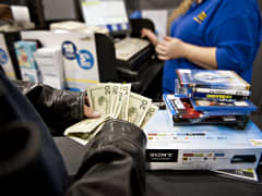 A customer counts his money as he prepares to pay for merchandise at a Best Buy Co. store in Preoria, Ill.