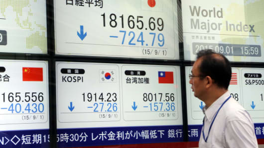 A businessman passes before a share prices board in Tokyo, Japan.