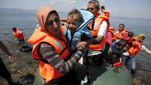 A Syrian refugee, from Kobani, carries her baby as she arrives with other Syrian refugees on a dinghy on the island of Lesbos, Greece August 23, 2015. Greece, mired in its worst economic crisis in generations, has been found largely unprepared for a mass influx of refugees, mainly Syrians. Arrivals have exceeded 160,000 this year, three times as high as in 2014.