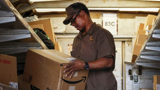 A UPS worker checks an Amazon box to be delivered in New York.
