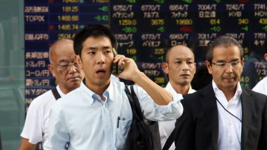 Businessmen pass before a share prices board in Tokyo on September 2, 2015. Japan's share prices fell 70.29 points to close at 18,095.40 points at the Tokyo Stock Exchange, giving up earlier gains as ongoing worries about China's economic woes weighed on the Asian market.