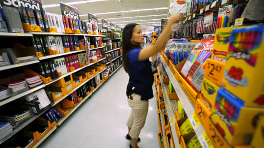 A Walmart department manager helps stock shelves with school supplies in San Diego, August 6, 2015.