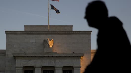 The silhouette of a pedestrian is seen walking past the Marriner S. Eccles Federal Reserve building in Washington, D.C