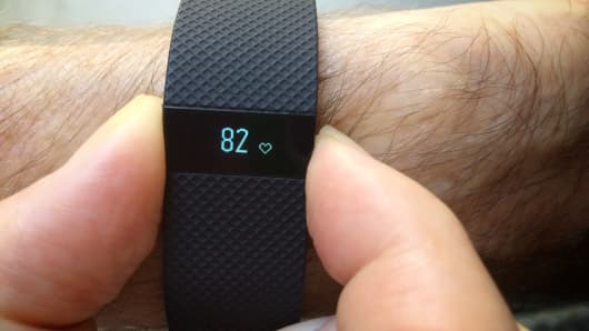 A man checks his heart rate on a FitBit Charge HR wearable activity tracker and monitor.