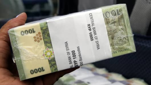 A bank official holds a bundle of new Syrian 1,000-pound bank notes.