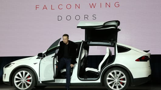 Tesla CEO Elon Musk demonstrates the falcon wing doors on the new Tesla Model X Crossover SUV during a launch event on September 29, 2015 in Fremont, California