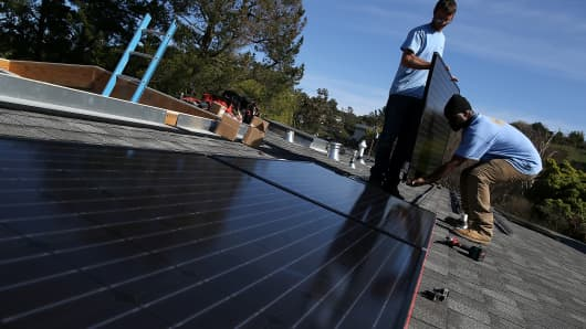 SolarCraft workers Craig Powell (left) and Edwin Neal install solar panels on the roof of a home on Feb. 26, 2015, in San Rafael, California.
