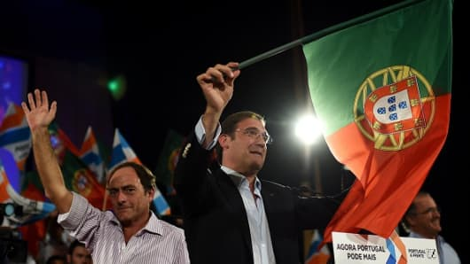 Portuguese Prime Minister Pedro Passos Coelho waves a Portuguese flag at a rally in September.