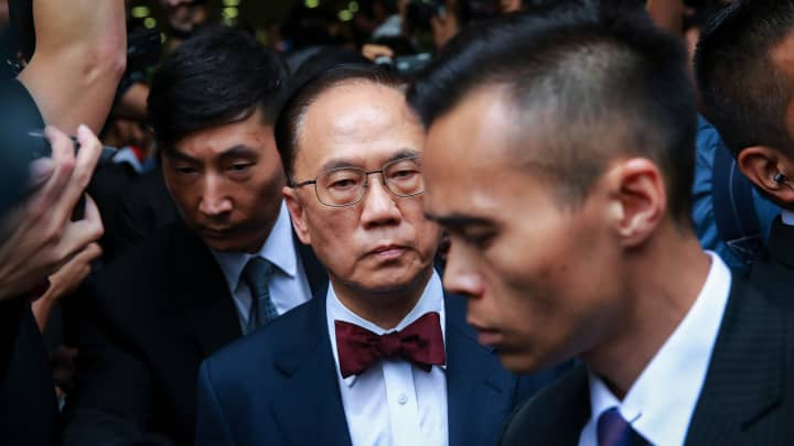 Donald Tsang, Hong Kong's former chief executive, center, leaves the Eastern Magistrates' Court in Hong Kong, China, on Monday, Oct. 5, 2015. Tsang, who completed his tenure as Hong Kong's No. 1 official in 2012, was charged with two counts of misconduct in public office, the anti-corruption bureau said.
