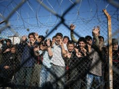 Immigrant minors peer out through the fence of an imm