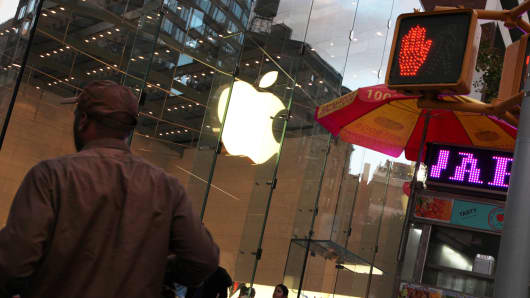 A pedestrian walks by an Apple store in New York.
