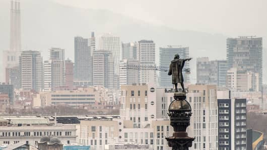Residential buildings and skyscrapers stand beyond a statue on the city skyline in Barcelona, Spain.