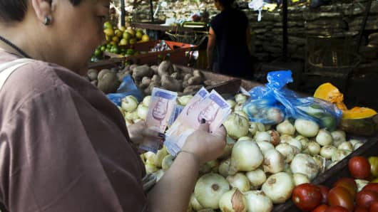 A woman counts bolivar notes as she pays for vegetables at a street market in Caracas on Oct. 1, 2015.