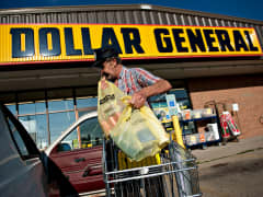 A shopper loads purchases into his vehicle outside a Dollar General Corp. store in Princeton, Illinois
