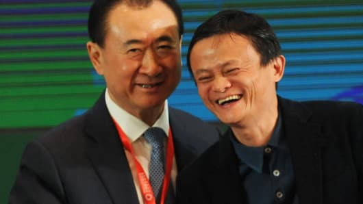 Wang Jianlin (L), chairman of the Dalian Wanda Group, shakes hands with Jack Ma, executive chairman of Alibaba Group last April.