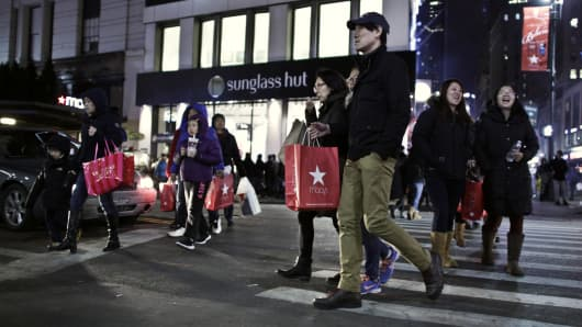 Customers walks outside Macy's Herald Square after the store opened its doors at 8 pm Thanksgiving day in New York City.