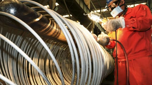 A worker polishes steel coils at a factory of Dongbei Special Steel Group in Dalian, China.