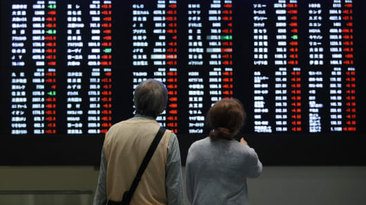 Visitors look at an electric stock board at the Tokyo Stock Exchange, operated by Japan Exchange Group, in Tokyo, Japan.