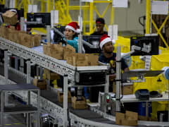 Amazon.com Inc. employees load boxes with merchandise at the company's fulfillment center