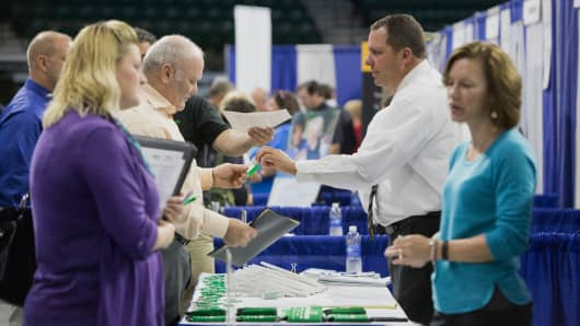 Job seekers, left, speak with recruiters during the Quad Cities career fair in Moline, Illinois.