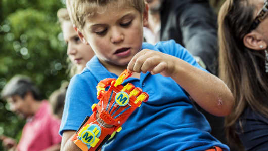 A young boy Maxence, born with a right hand malformation, examines his new 3D-printed hand given to him by the Association for the Study and Assistance of Child Amputees (ASSEDEA) on August 17, 2015 in Cessieu.