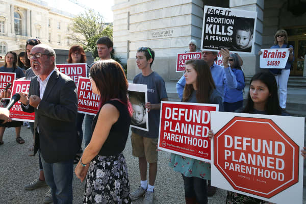 Protesters hold signs protesting Planned Parenthood in front of the Longworth House Office Building on Capitol Hill September 16, 2015 in Washington, DC.