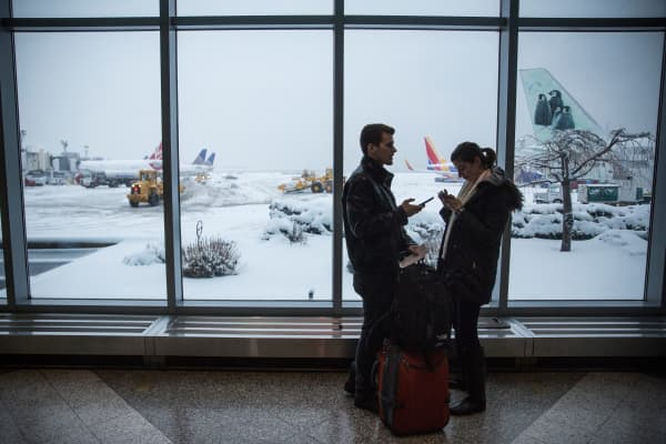 Travelers check their phones while waiting for a flight at La Guardia Airport during a winter storm on Feb. 2, 2015, in Queens, New York City.