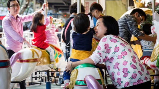 Adults and children ride on a carousel at Lu Xun Park in Shanghai, Oct. 24, 2015.