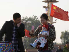 A couple takes pictures with their baby on the Tiananmen Gate in Beijing November 2, 2015. China must continue to enforce its one-child policy until new rules allowing all couples to have two children go into effect, the top family planning body said.