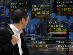 A pedestrian walks in front of a share prices board showing the numbers on the Nikkei 225 at the Tokyo Stock Exchange (top C) in Tokyo