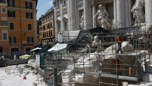 Workers carry out restoration work on the Trevi Fountain in central Rome on July 24, 2015.