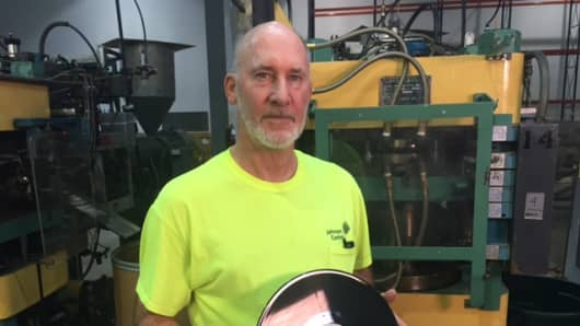 Dave Miller, plant manager of Independent Record Pressing in New Jersey, with a finished record.